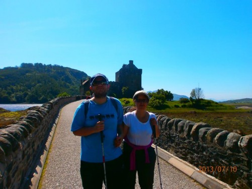 Tony and Tatiana on the path leading over a bridge to the island and castle of Eilean Donan. The island is located in Loch Duich in the western Highlands.