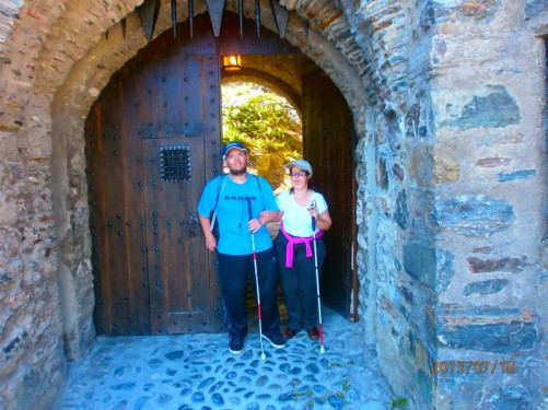 Tony and Tatiana standing in a doorway through a thick stone wall in the castle grounds. The spikes of the bottom of a portcullis can be seen above.