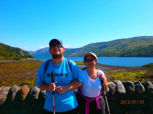 Tony and Tatiana by a stone wall in the castle grounds. A picturesque view of Loch Duich behind.