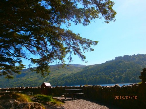 A path with picnic tables. Wooded scenery at the side of the loch.