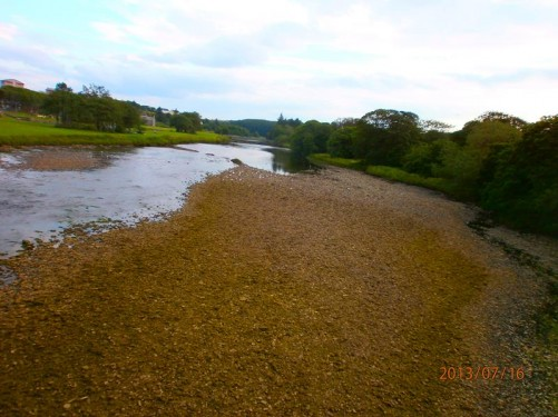 View along the Thurso River from the bridge. The river level in quite low and lots of gravel can be seen on the exposed river bed.
