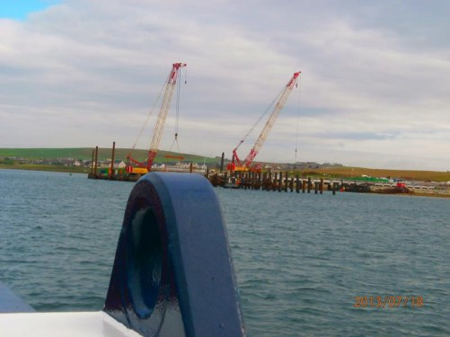 On-board a ferry leaving Stromness for a day trip to Hoy. Looking towards a pair of large cranes on a nearby quay.