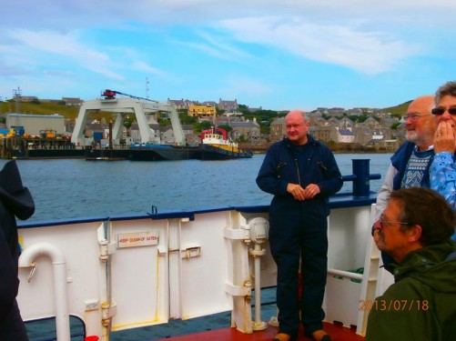 Passengers and a male crew member on the deck of the ferry. Stromness Harbour in view.