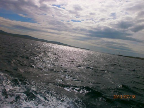 View across the sea, sunlight reflecting on the water. Hoy Lighthouse, located on Greensay, visible in the distance.