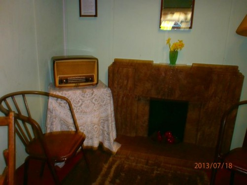 Re-creation of a 1940s living room. Fireplace, wooden chairs, table with a radio on it.