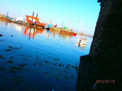Stromness harbour. Cranes and a mechanical digger (possibly for dredging) on the opposite side.