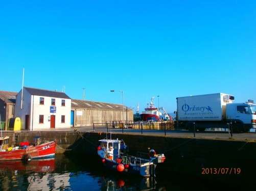 View from a quay in the harbour. A pair of small fishing boats moored in front. Larger boats visible further away.