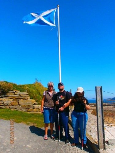 Tatiana, Tony and Jan, in front of a pole flying the Scottish flag on Brough of Birsay.