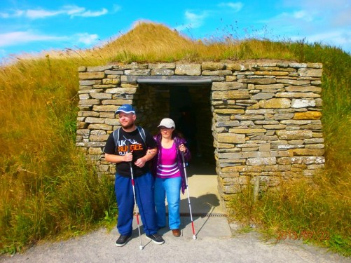 At the entrance to a rebuilt stone house. The roof covered with earth and grass.
