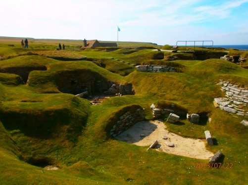View across part of Skara Brae. Pitted grassy landscape containing the remains of Neolithic houses.