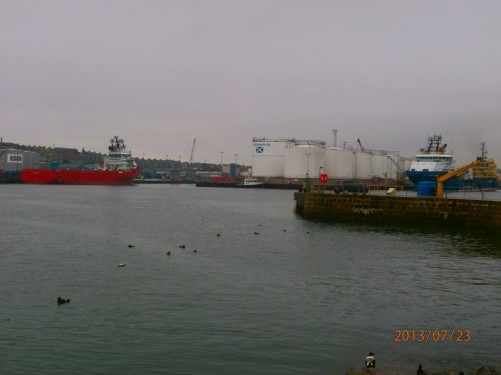 View across the harbour. Cargo ships moored. 'Aberdeen Oil' storage tanks over on the opposite side.