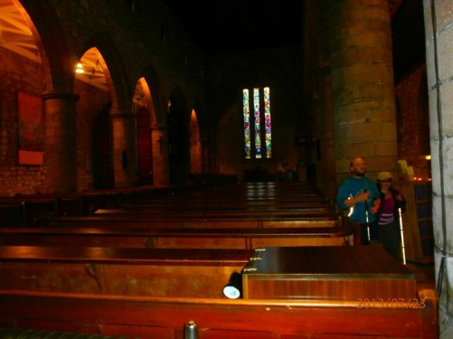 Tony and Tatiana inside the Cathedral Church of St Machar. They are standing in a side aisle next to rows of wooden pews.