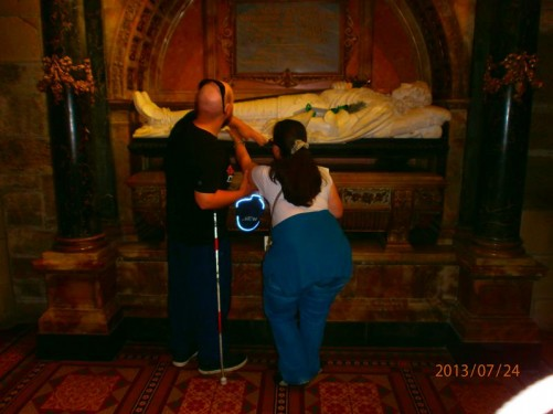 Tatiana and Tony touching a large tomb. The tomb is of James Graham, 1st Marquis of Montrose (1612–1650). A white marble carving of James Graham lies on top of the tomb, he is clad in armour, holding his sword flat against his chest.