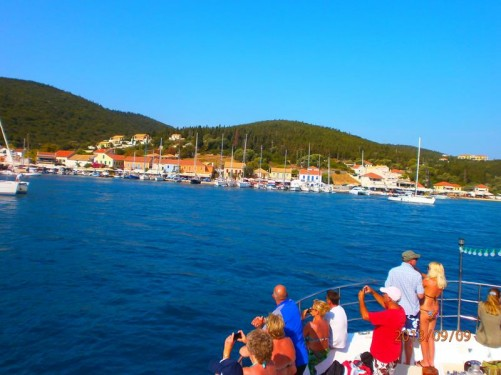 Approaching the fishing village of Fiskardo, the northernmost port of Kefalonia. Boats moored along the sea front.
