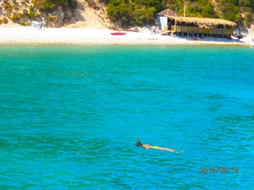 Swimming stop on the Ithaki cruise. Looking towards a sandy beach. Person snorkelling in the sea in front.