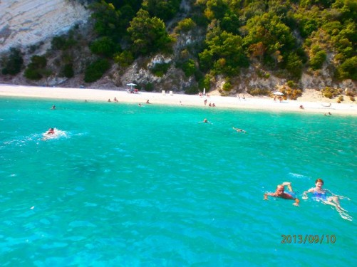 Another view from the boat towards the sandy beach. People swimming in the sea.