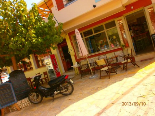 A small square with a café at the side. Tables outside.