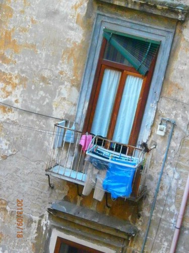 Washing hanging to dry from a balcony above a narrow street.