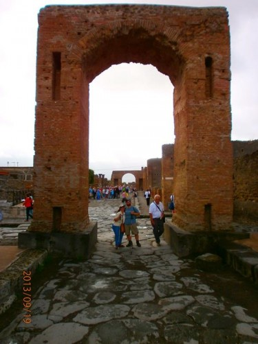The Arch of Caligula. Tatiana and Tony standing underneath. The Arch of Nero is also visible further along the street.