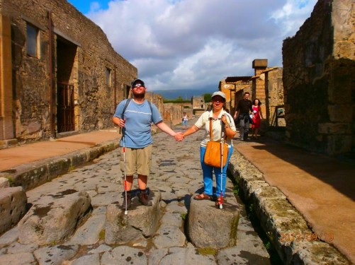 Tatiana and Tony stood on rectangular stone blocks in one of the main streets. These allowed pedestrians to cross the street without having to step onto the road itself which doubled up as Pompeii's drainage and sewage disposal system. These blocks also allowed horse-drawn carts carrying goods to use the streets. Mount Vesuvius is in background, but mostly obscured by cloud.