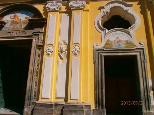 A pair of doorways into the baroque style church. The building dates from the 15th century. The exterior is painted in yellow and white.