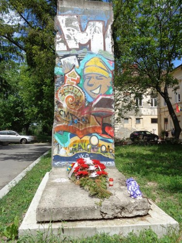 A concrete segment of the Berlin Wall outside the Memorialul Revolutiei. There is a wreath laid in front of it.  The museum is located in old army barracks located off Strada Popa Șapcă just north of the centre.