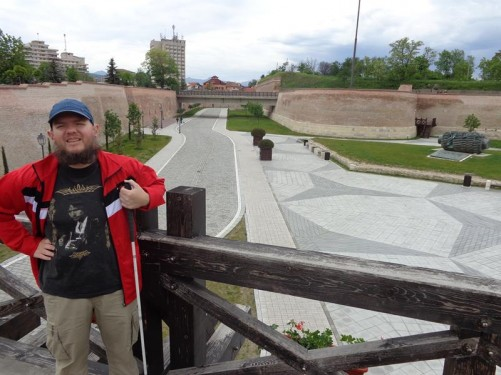 Tony on the bridge with a view of the rampart walls extending behind him.