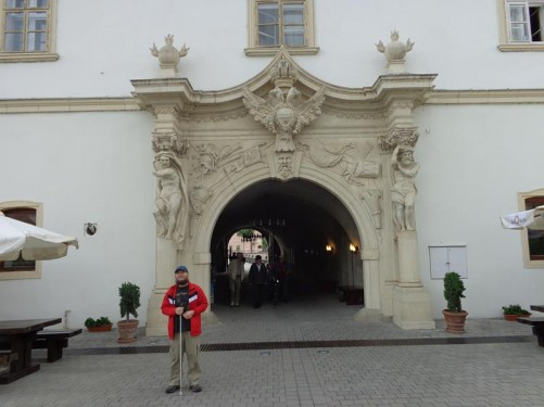 Tony at the inside of Poarta IV (4th Gate). This gate passes along a passageway through the middle of a building. The inside entrance is decorated with stone carving, including a double-headed eagle, the coat of arms of the Austrian Empire, in the top middle. There are male statues on plinths at either side.