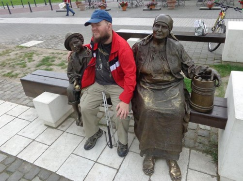 Tony sitting on a bench between two more bronze statues: on one side a peasant woman holding a container of eggs and on the other a boy holding a single egg.