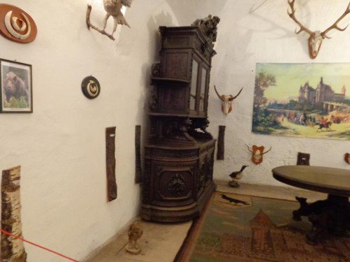 A large table and kitchen dresser, part of another museum display. Also stuffed birds and skulls of deer and other animals on the walls.