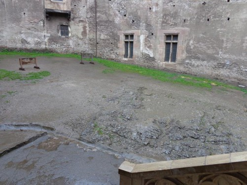 Looking into the inner courtyard. A pair of wooden stocks at the far side.
