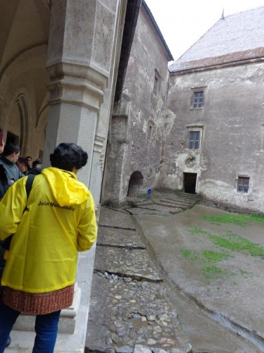 Another view of the courtyard. Buildings around the sides, the stone walls partly covered with render or plaster. The ground wet and quite muddy due to the rain.