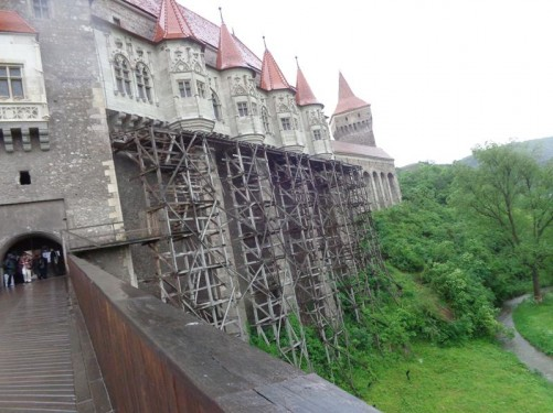 View of the castle's exterior. The Zlaști River flowing in a natural moat below. Tall stone walls of the castle rising up from the edge of the moat. A row of four small round towers protruding near the top of the walls.