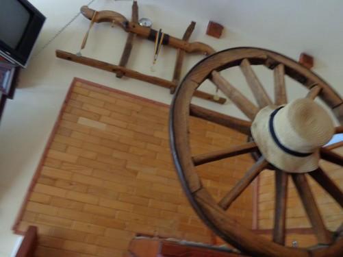 A hat hanging on a cart wheel inside Hostel La Padre.