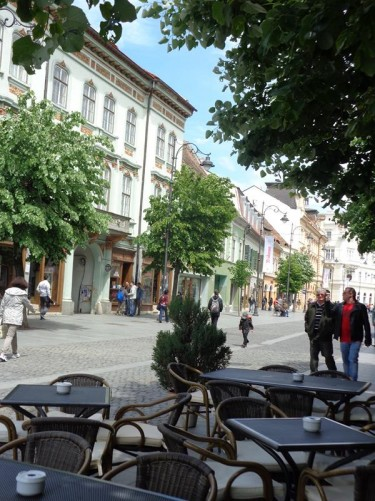 Further along Strada Nicolae Bălcescu. A group of café tables in front. Again an attractive mix of historic buildings, mostly Germanic in style.