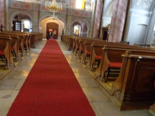 Inside the Roman Catholic Church looking along the central aisle towards the main entrance. The aisle has a red carpet along its length with rows of wooden pews at either side.