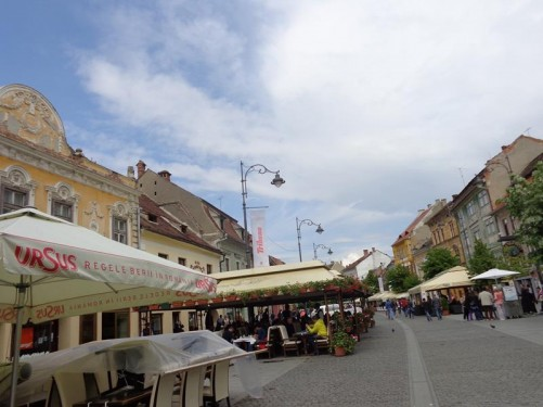 Another view along Strada Nicolae Bălcescu. People sitting at outdoor café tables.