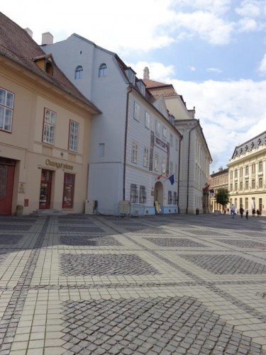 The northwest corner of Grand Square. The very pale blue building in front is the Casa Albastra (Blue House) or Moringer House, another baroque building dating from the 18th-century. The old coat of arms of Sibiu is on its façade. Today the building is part of the Brukenthal Museum and houses a collection of Romanian artwork.