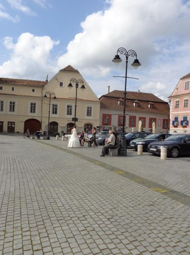 Looking towards the northwest corner of Small Square, which like Grand Square is lined with historic buildings, but here they are somewhat smaller and less grand. A bride can be seen standing a little way across the square with smartly dressed family or friends sitting on benches along side.