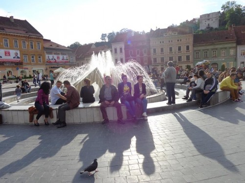 Lots of people sitting on benches and around the fountain in Council Square. Taken in the late afternoon.