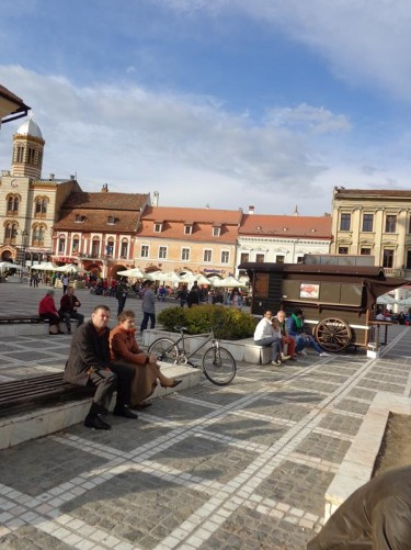 Another view across Council Square. Historic buildings in various styles on the opposite side, including the Romanian Orthodox Cathedral visible on the far left. The cathedral has a domed tower on its roof.