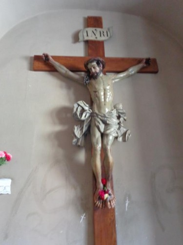 A statue of Christ on the cross, mounted on a wall inside the cathedral.