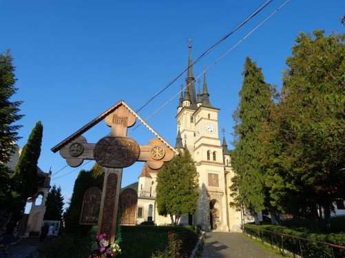 In the churchyard of St. Nicholas Orthodox Church. A wooden cross with flowers left near the base in front.