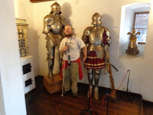 Tony standing between two old suits of armour.