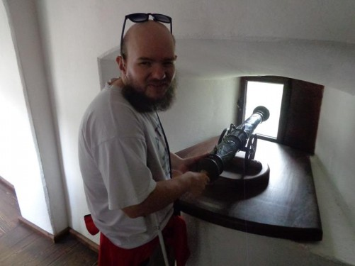 Tony touching the end of a miniature canon, which is pointing through a window.