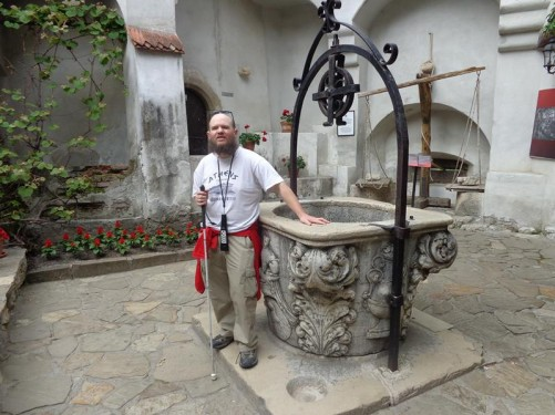 A wishing well in the castle's interior courtyard. Decorative stone carving around the base. Tony standing at one side.