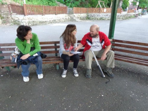 Tony sitting on a bench with Andrea and her mum Viorica.