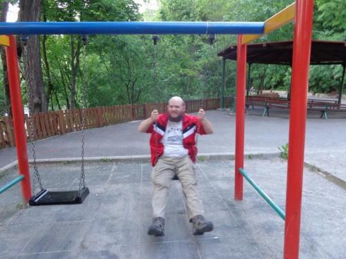 Tony sitting on a swing.