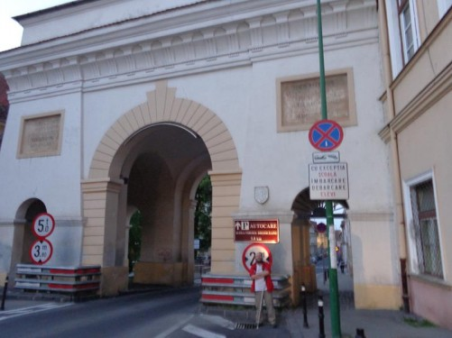 In front of Șchei Gate (Poarta Șchei). The gate resembles a triumphal arch with three openings. Rebuilt in 1827.