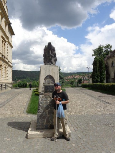 Tony in front of a bust of Vlad Tepes (Vlad the Impaler) on top of a stone column.